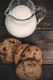 Milk and homemade biscuits. Homemade corn and oat biscuits with chocolate and milk in glass jug Stock Photo