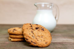 Milk and homemade biscuits. Milk in glass jug and homemade chocolate  biscuits Stock Photos
