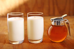 Milk and honey. Two glasses of milk and a jar of honey against wooden background royalty free stock photo