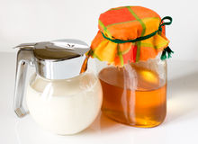 Milk and honey. Milk and illuminated honey can Stock Photo