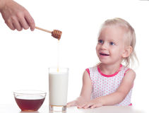 Milk with honey. Mother pours honey in milk little girl Stock Photos