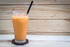 Milk ice tea on wooden background. Milk ice tea on a wooden background Royalty Free Stock Image