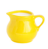 Milk in jug. Yellow pitcher with milk on white isolated Royalty Free Stock Image