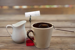 A milk jug and a cup of black coffee Stock Image