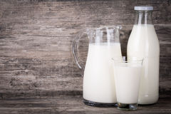 Milk in jug, glass and bottle on wooden background. Milk in a group of jug, glass and bottle on dark wooden background Royalty Free Stock Photography