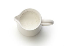 Milk jug with milk. Top view of milk jug with milk on the white royalty free stock photos