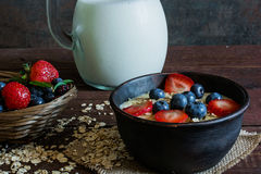 Milk in a jug and oatmeal porridge with fresh ripe berries Royalty Free Stock Image