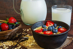 Milk in a jug and oatmeal porridge with glass of milk in a pottery bowl with fresh ripe berrie Royalty Free Stock Photos