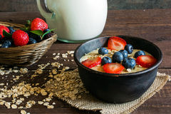 Milk in a jug and oatmeal porridge in a pottery bowl with fresh ripe berries in a wicker bowl Stock Photography
