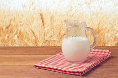 Milk jug over wheat field background Stock Photo