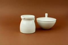 Milk jug with sugar bowl brown background.  Stock Photo