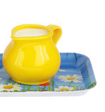 Milk in jug on tray. Yellow pitcher with milk on tray isolated Royalty Free Stock Photography
