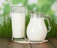 Milk jug on wooden desk Stock Images