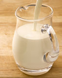 Milk jug on wooden table Royalty Free Stock Image