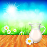Milk jug on wooden table, nature background Royalty Free Stock Image