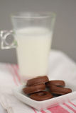 Milk and little chocolate donuts. Glass of milk with little chocolate donuts, snack over white and pink tablecloth Royalty Free Stock Image