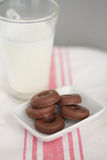 Milk and little chocolate donuts. Glass of milk with little chocolate donuts, snack over white and pink tablecloth Stock Images