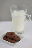 Milk and little chocolate donuts. Glass of milk with little chocolate donuts, snack over white tablecloth Stock Photography
