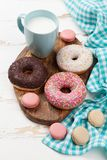 Milk, macaroons and donuts. On wooden table Royalty Free Stock Photos