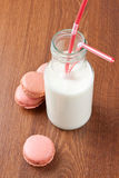 Milk and macaroons. Some french macaroons with a bottle of milk Stock Images