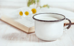 Milk in metal mug and chamomile flowers in open book Stock Image
