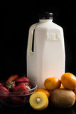Milk and mix fruits on the black. Stock Photography