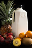 Milk and mix fruits on the black. Stock Image