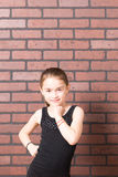 Milk Moustache Muscles. Beautiful young girl with milk moustache flexing muscles against brick wall background stock images