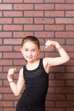 Milk Moustache Muscles. Beautiful young girl with milk moustache flexing muscles against brick wall background stock photo