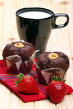 Milk, muffins and strawberries for breakfast. Black cup of milk with chocolate muffins and strawberries on pine wood Stock Image