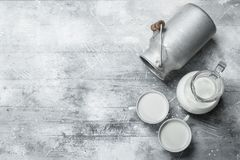 Milk in mugs with a can. On a rustic background stock photo