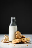 Milk and oatmeal cookies. Bottle of milk with pile of oatmeal cookies with raisins on brown paper bag Stock Image