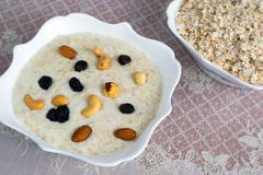 Milk oatmeal with nuts and raisins Royalty Free Stock Photo