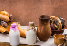 Milk, pitcher, cup and bread loaves Stock Photography