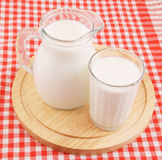 Milk in pitcher and glass with wooden board Stock Photography