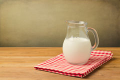 Milk pitcher on tablecloth on a grunge background Stock Photo