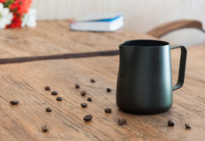 Milk pitcher on wooden coffee table Royalty Free Stock Photo