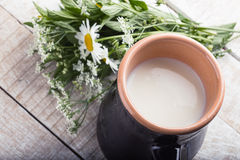 Milk in pitcher on wooden table royalty free stock photography