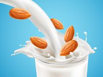 Milk plashing effect with liquid pouring down in glass cup with flying almond kernels isolated on blue background. Design element for advertising beverages Royalty Free Stock Images