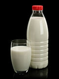 Milk in a plastic bottle and a glass. Is isolated on black Royalty Free Stock Image
