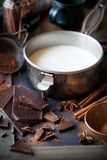 Milk in a pot, dark chocolate, cinnamon and star anise Royalty Free Stock Photography