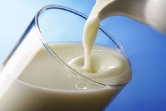 Milk pour in glass Stock Images