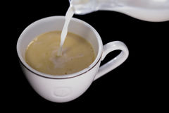Milk poured in a Cup of coffee Royalty Free Stock Image