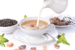 Milk poured in a cup of tea Royalty Free Stock Images