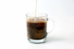 Milk poured into a transparent cup of black coffee Stock Photography