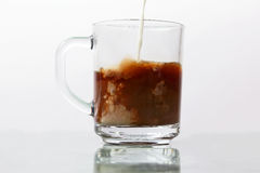 Milk poured into a transparent cup of black coffee Royalty Free Stock Photography
