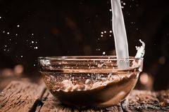 Milk pouring into bowl with balls. Royalty Free Stock Photo