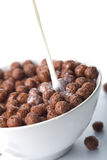 Milk pouring into bowl with chocolate balls Stock Images