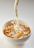 Milk pouring into bowl with corn flakes Royalty Free Stock Photography