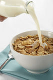 Milk pouring into cereal bowl. A tabletop view of milk being poured from a bottle into a bowl of cereal flakes Royalty Free Stock Images
